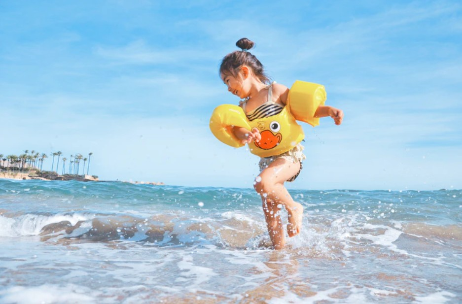a happy little girl playing on the beach