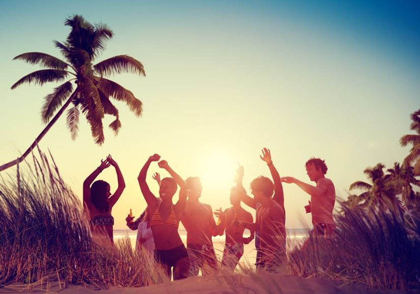 beach party, people in swimwear, white sand, grass, sea, coconut trees
